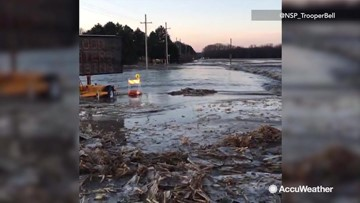 Highway flooded with fast-flowing river