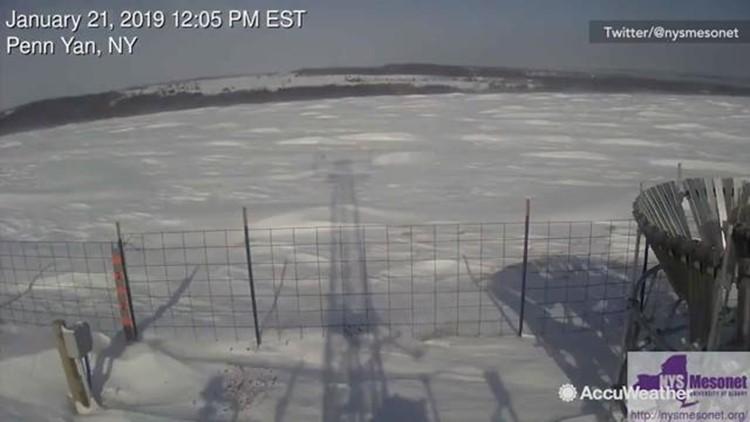 Heavy wind sends waves of snow rolling across field